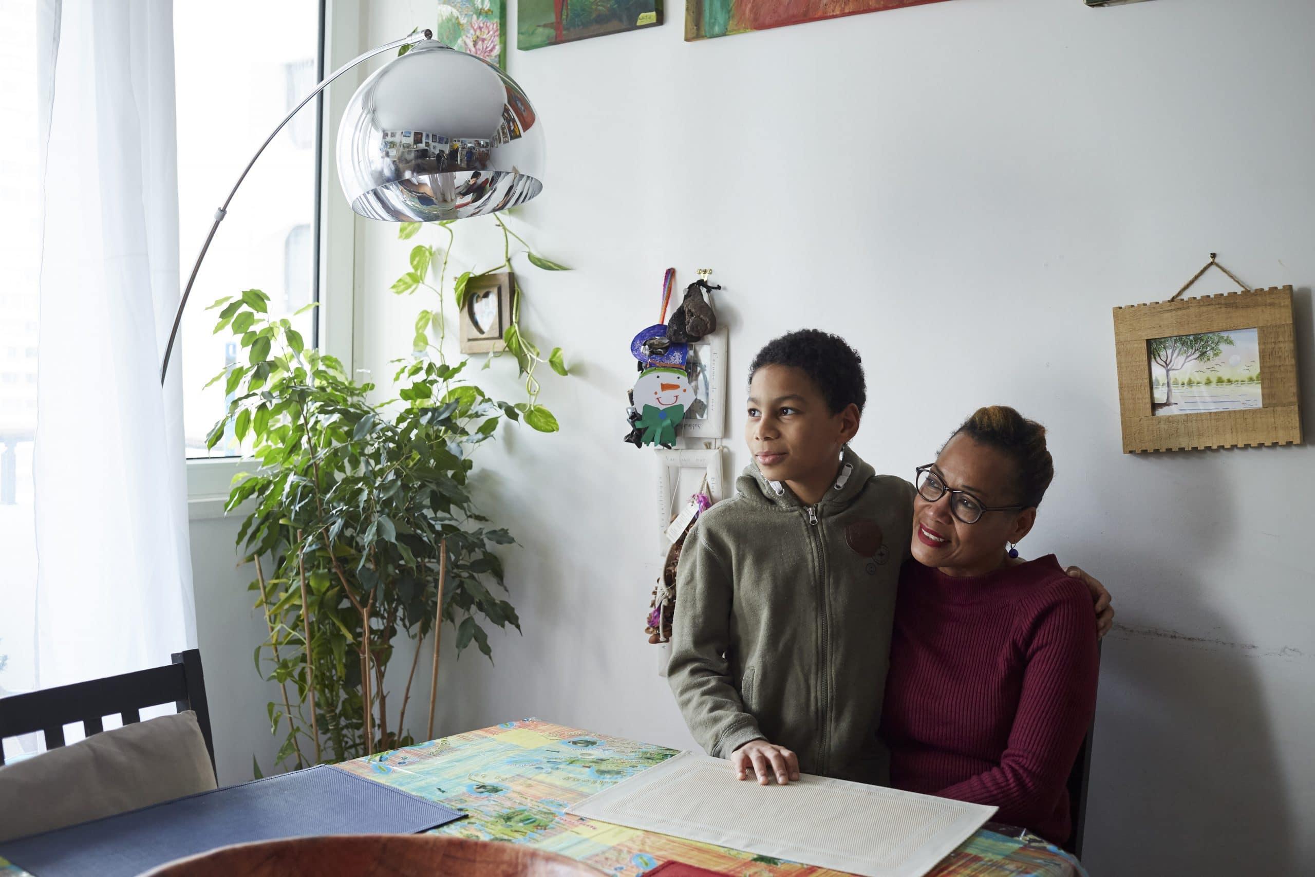 Un petit garçon dans les bras de sa mère dans un appartement