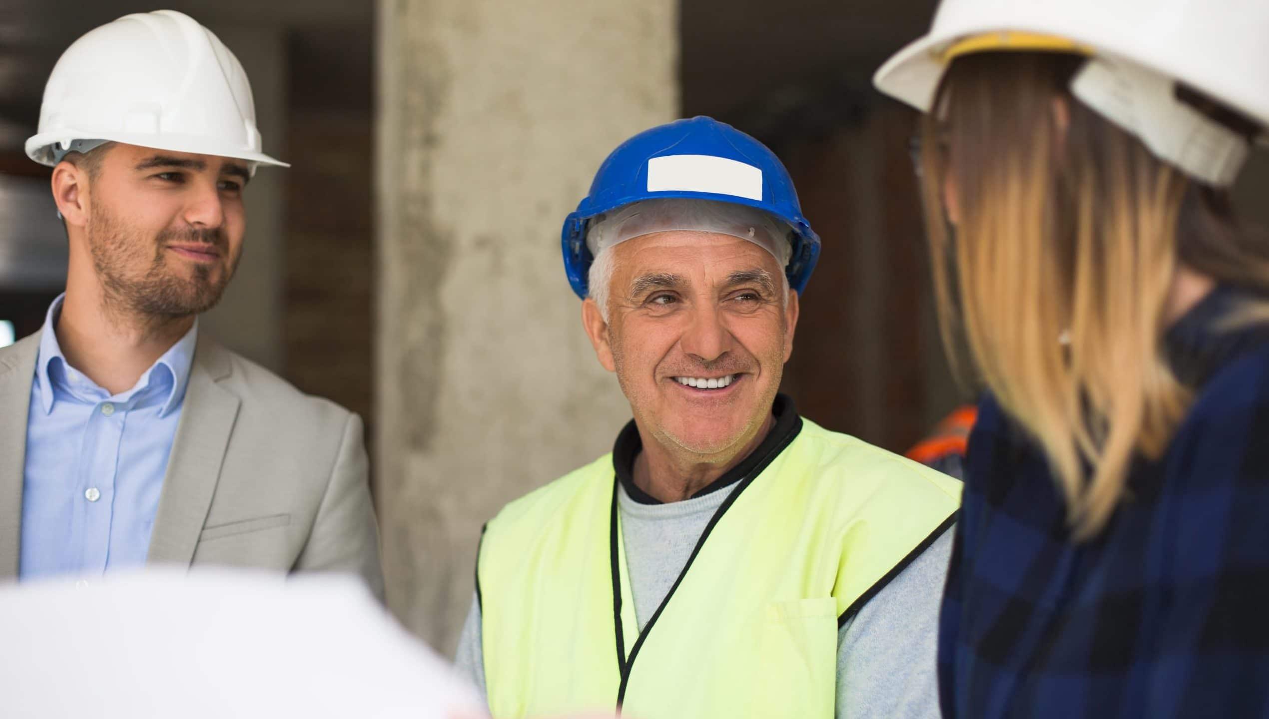 Deux hommes et une femme avec un casque de chantier échangent